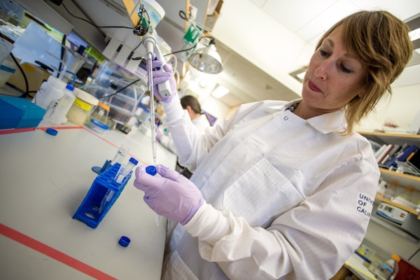 A woman in a white lab coat holding a pipet at a bench in the laboratory.